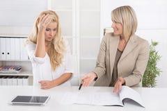 年轻女性实习生犯了一个错误在工作和她的上司crit 免版税库存图片
