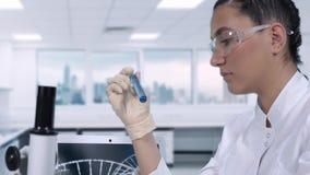 女性实验员进行蓝色液体的实验室试验在试管的,当坐在a时的一张桌上 股票视频
