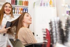女性客户的美发师干毛发 免版税库存图片