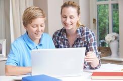 女性家庭有研究的家庭教师帮助的男孩使用便携式计算机 免版税库存照片