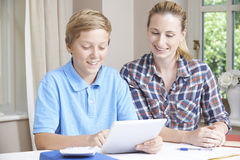 女性家庭有研究的家庭教师帮助的男孩使用数字式片剂 图库摄影