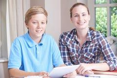 女性家庭有研究的家庭教师帮助的男孩画象使用开掘 免版税库存照片