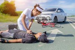 女性对亚洲骑自行车者的护士帮助的紧急CPR受伤 免版税库存照片
