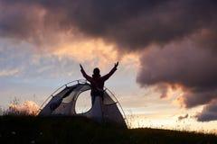 女性对享受在山的天空的登山人举的手惊人的日落在罗马尼亚 免版税库存图片