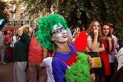 女性小丑绿色假发的和有在一根棍子的心脏的在马戏团演员`马戏列队行进`游行在伏尔加格勒 免版税库存照片