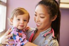 女性小儿科医生举行的女孩 免版税库存图片