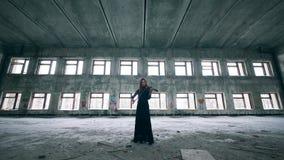 女性小提琴手弹奏在一个不整洁的大厦的仪器 股票视频