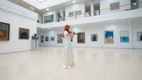 女性小提琴手弹奏在画廊的仪器 影视素材