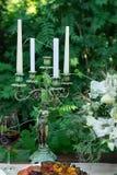 以女性小雕象的形式古色古香的烛台在绿色背景的一张桌上 库存照片