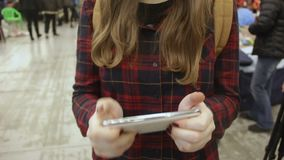 女性少年的手使上瘾对使用在人群的智能手机的赌博 股票视频