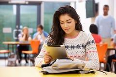 女性少年学生在有数字式片剂的教室 免版税库存照片
