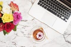 女性工作场所概念 自由职业者的在舱内甲板的时尚舒适的阴物工作区放置与膝上型计算机,茶,在丝毫的花的样式 图库摄影