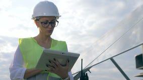 女性工程师与片剂在太阳电池板附近,关闭一起使用 影视素材