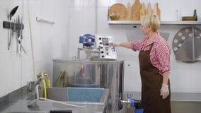 女性工艺师在一绝尘室和出去编程自动微型乳酪厂机器 股票视频