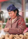女性市场供营商卖在一个传统市场,北京,中国上的土豆 免版税库存图片