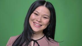 女性年轻可爱的亚洲人特写镜头射击转动快乐微笑和看直接照相机与背景 影视素材