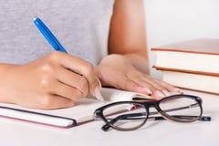 女性年轻学生在笔记本写在教室 免版税图库摄影