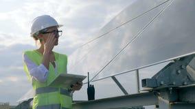 女性建设者在一个太阳能电池附近站立并且与她的片剂一起使用 股票视频