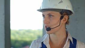 女性建造者工程师考虑新建工程的一个计划并且通过话筒谈话 免版税库存照片
