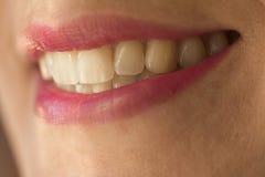 女性微笑宏观射击与牙和桃红色唇膏的 免版税库存照片