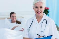 女性微笑对照相机的医生和孕妇 免版税图库摄影