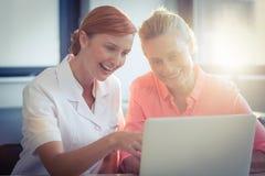 女性微笑护士和资深的妇女,当使用膝上型计算机时 库存照片