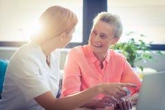 女性微笑护士和资深的妇女,当使用膝上型计算机时 免版税库存图片