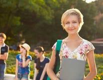 女性微笑的学生户外在与朋友的晚上 免版税库存照片