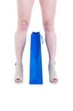 女性性感的腿和蓝色购物袋特写镜头  免版税库存照片