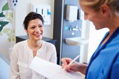 女性患者和Have Consultation In医生医房 免版税图库摄影