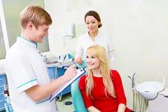 女性患者在牙医办公室,回答的医生问题 库存图片