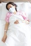 女性患者在医院病床上 免版税库存图片