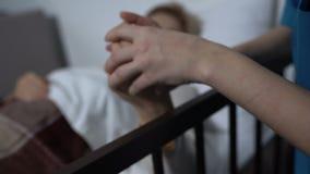 女性患者睡着与电视,关心盖她的护士用毯子 影视素材
