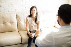女性患者谈论她的麻烦与心理学家 库存图片