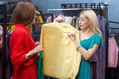 给女性愉快的户内看起来的模型顾客购物微笑的存储妇女穿衣的亚洲美丽的白种人衣裳 库存图片
