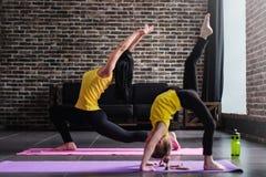 年轻女性成人做的新月形刺姿势和站立在单腿被倒置的职员位置的女孩孩子在瑜伽期间 免版税图库摄影