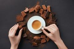 女性手、咖啡,块菌和巧克力灰色表面上 免版税库存照片