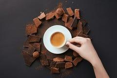 女性手、咖啡,块菌和巧克力灰色表面上 库存图片