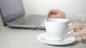 女性手、膝上型计算机和咖啡
