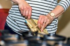 女性手不耐烦地打开与刀子的很好被包装的圣诞礼物 库存照片