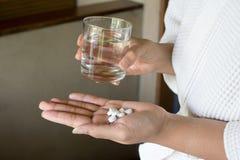 女性手举行医学片剂和玻璃 图库摄影
