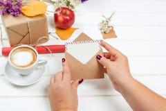 女性手举行礼品券 礼物盒,杯子在秋天背景的热奶咖啡 库存图片