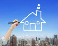 女性手候宰栏图画房子形状在天空覆盖 图库摄影
