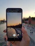 女性手做图片城市日落在您的智能手机 O 免版税库存图片