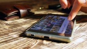 女性手关闭她的智能手机和汽车采取钥匙  库存照片