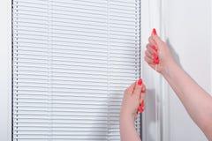 女性手关闭窗帘在窗口 免版税库存图片