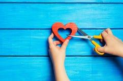 女性手削减了与剪刀的木红色心脏在蓝色背景 破坏联系的概念,争吵,离婚 p 免版税库存图片