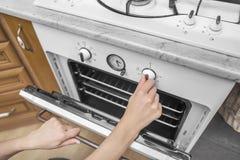 女性手包括烤箱 免版税库存图片