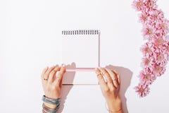 女性手和一个笔记本有一支桃红色铅笔的 库存图片
