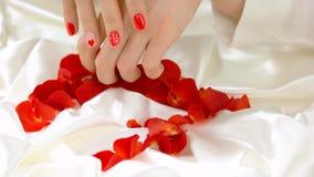 女性手和玫瑰花瓣在白色丝绸 股票视频